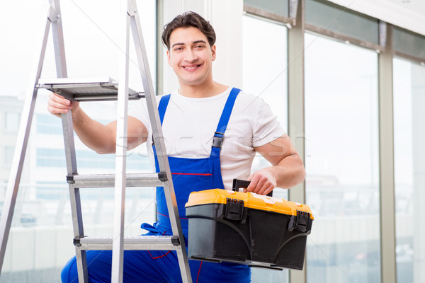 Young repairman climbing ladder at construction  site Stock photo © Elnur