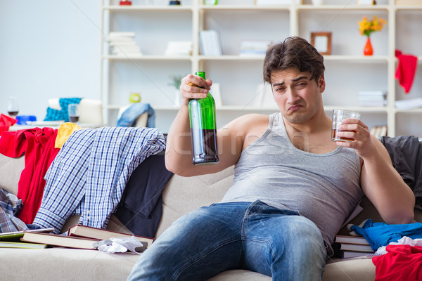 Young man student drunk drinking alcohol in a messy room Stock photo © Elnur