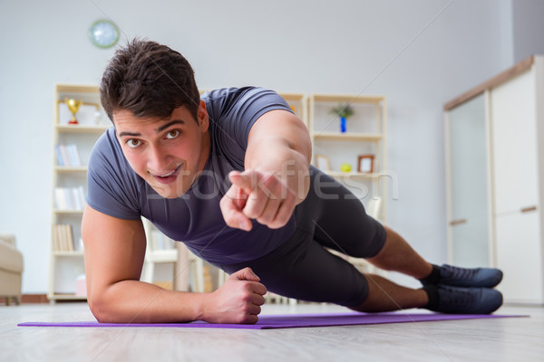 Young man exercising at home in sports and healthy lifestyle con Stock photo © Elnur