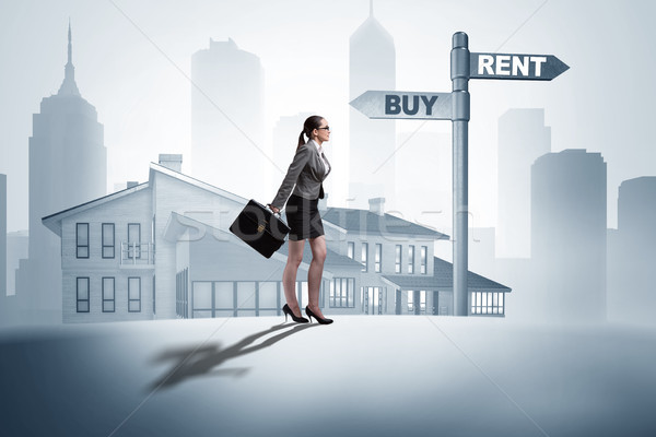 Businesswoman at crossroads betweem buying and renting Stock photo © Elnur