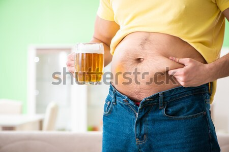 Fat obese man holding beer in dieting concept Stock photo © Elnur