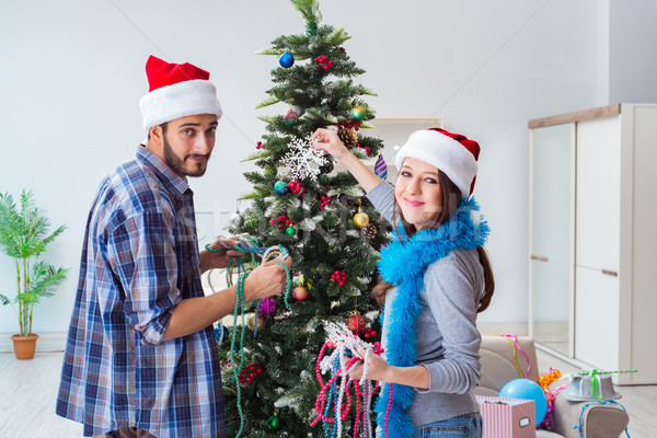 The young family decorating christmas tree on happy occasion Stock photo © Elnur