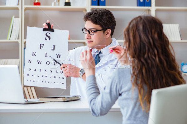 Doctor optician with letter chart conducting an eye test check Stock photo © Elnur