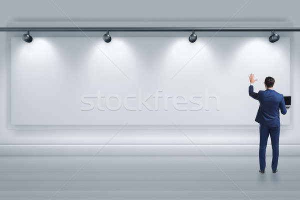 Businessman pressing virtual button on the wall lit with spotlig Stock photo © Elnur