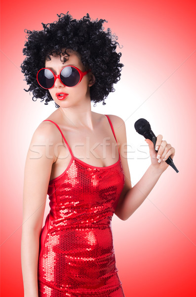 Pop star with mic in red dress on white Stock photo © Elnur