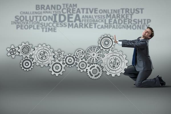 Businessman with cogwheels gear in teamwork concept Stock photo © Elnur