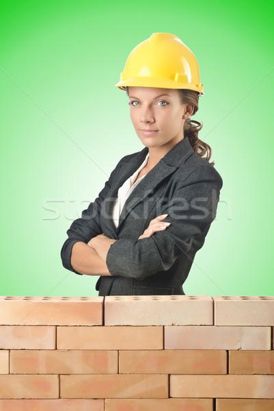 Young female builder near brick wall Stock photo © Elnur