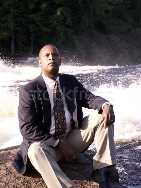 Homem de negócios terno sessão rocha rio Foto stock © elvinstar