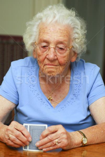 Idős hazárdjáték nő tart kártyák néz Stock fotó © elvinstar