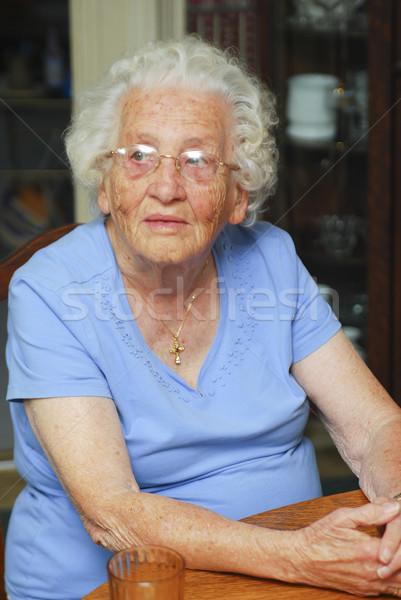 Senior mulher sessão tabela olhando Foto stock © elvinstar