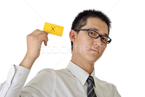 X sign on yellow card holding by business man, closeup portrait of Asian on white background. Stock photo © elwynn