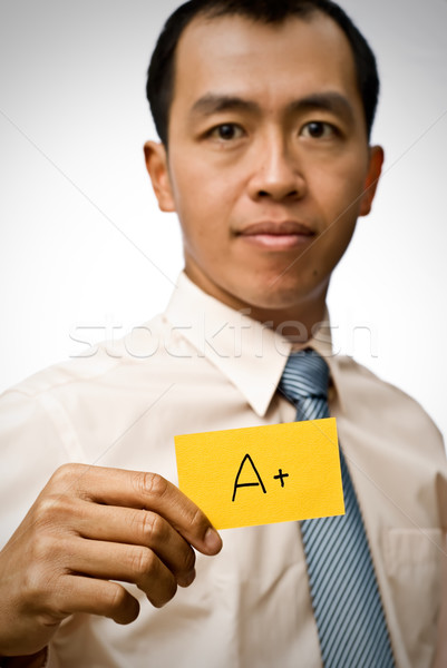 A plus sign on yellow card holding by businessman of Asian. Stock photo © elwynn