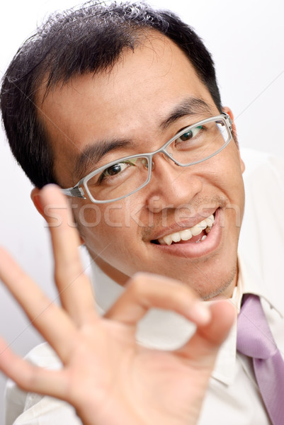 Businessman of Asian showing OK gesture and smiling. Stock photo © elwynn