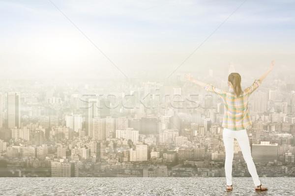 Fiatal nő nyújtott karok néz város fiatal Stock fotó © elwynn