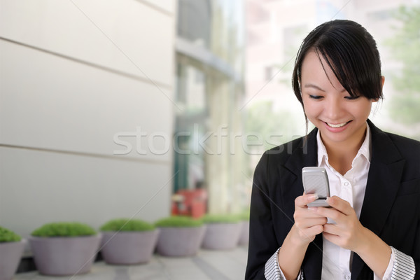 Happy business woman reading SMS Stock photo © elwynn