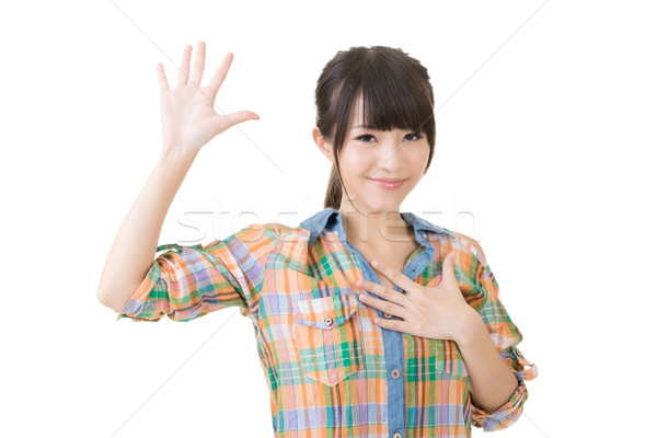 Asian young woman give a gesture of swear Stock photo © elwynn