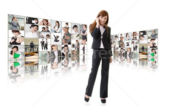 üzlet globális kommunikáció üzletasszony beszéd mobiltelefon videofal Stock fotó © elwynn