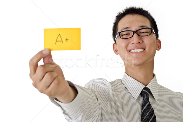 Happy business man holding A+ yellow card and smiling, closeup portrait focus on face against white  Stock photo © elwynn