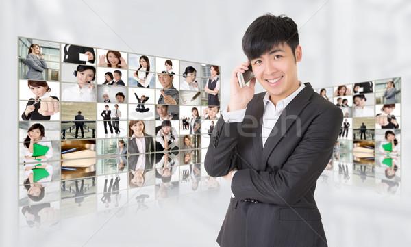 Fiatal üzletember beszéd telefon áll tv Stock fotó © elwynn
