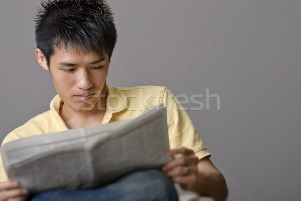 Asian young man reading newspaper Stock photo © elwynn