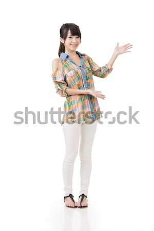 Young asian woman shows or introduce something Stock photo © elwynn