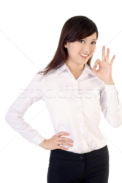 Ok gesture by business woman of Asian on white background. Stock photo © elwynn