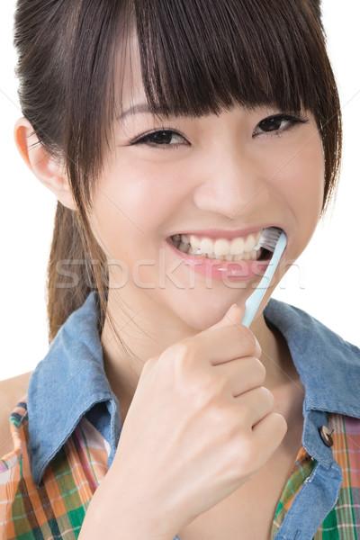 Closeup portrait of woman brushing teeth Stock photo © elwynn