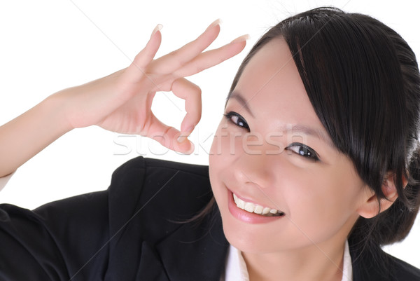 Business woman show ok gesture with delight expression, closeup portrait on white background. Stock photo © elwynn