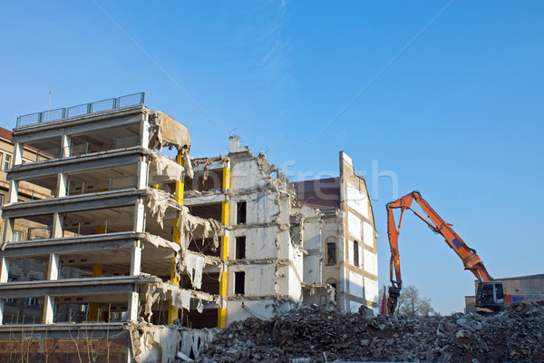 Demolition of a building with excavator Stock photo © elxeneize