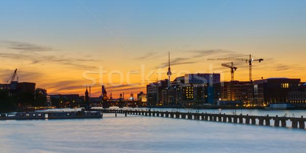 Naplemente panoráma Berlin folyó égbolt híd Stock fotó © elxeneize