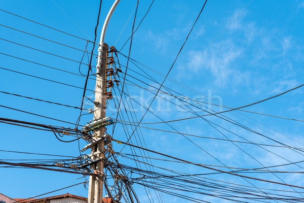 Electric post with a lot of wires Stock photo © elxeneize