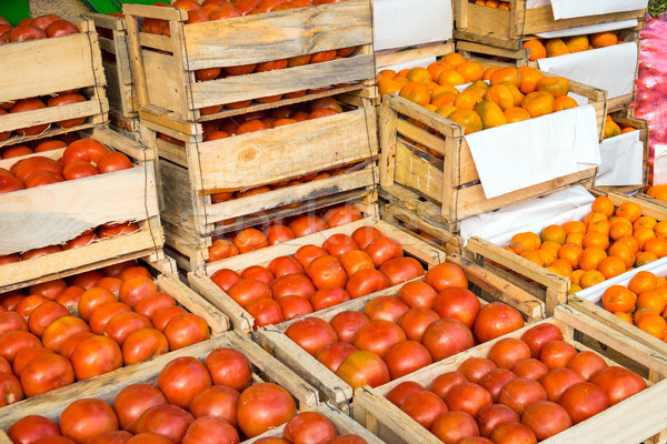 Tomatoes and tangerines in wooden boxes for sale Stock photo © elxeneize