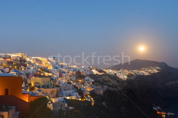 The moon rises over Oia Stock photo © elxeneize