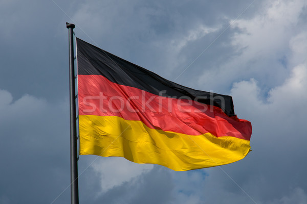 German flag in front of dark clouds Stock photo © elxeneize