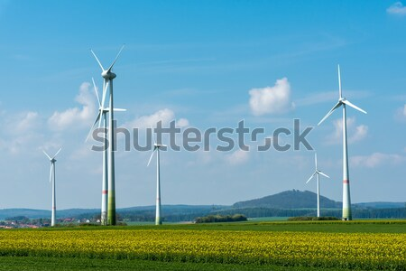 Wind energy plants in a rapeseed field Stock photo © elxeneize