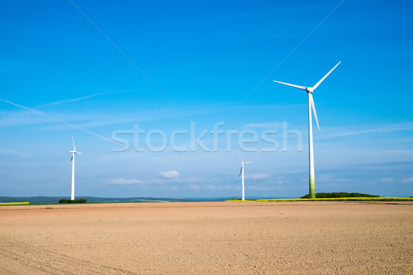 Windwheels behind a barren field Stock photo © elxeneize