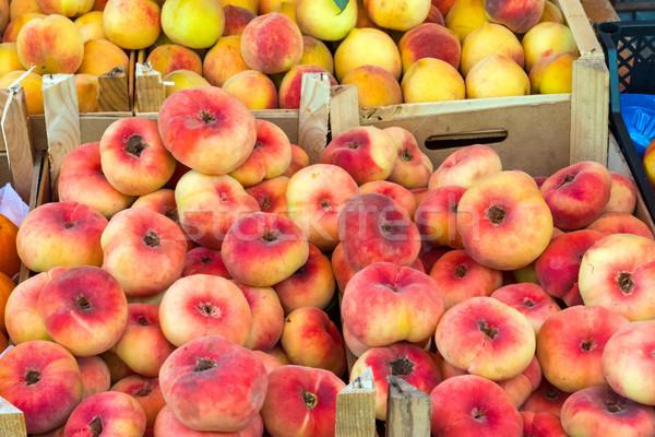 Különböző őszibarackok vásár piac gyümölcs piros Stock fotó © elxeneize