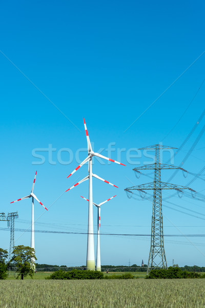 Overhead lines and wind engines on a sunny day  Stock photo © elxeneize