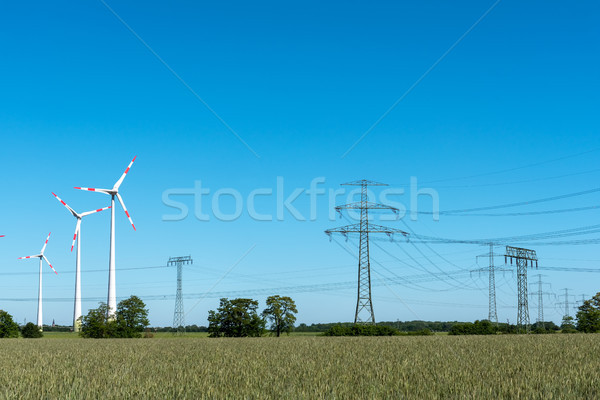 Overhead lines and wind turbines on a sunny day Stock photo © elxeneize