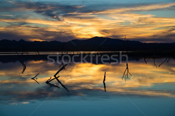 Laatste gloed zonsondergang meer water wolken Stockfoto © emattil
