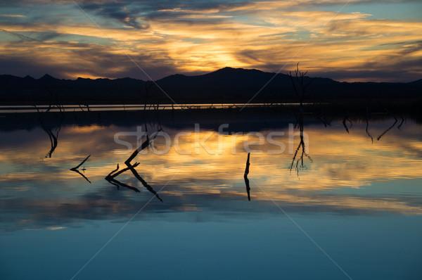 Gün batımı yansımalar su bulutlar mavi dağlar Stok fotoğraf © emattil