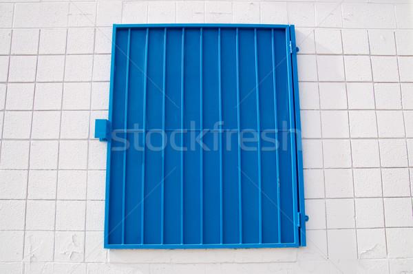 Blue mesh shutter on white wall Stock photo © emattil