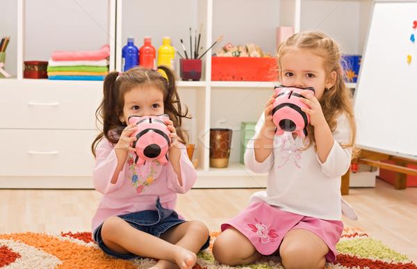 Little girls kissing the piggybanks Stock photo © emese73