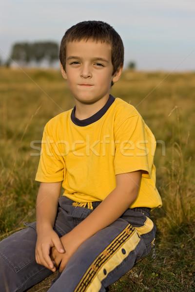 Garçon séance herbe sourire Photo stock © emese73