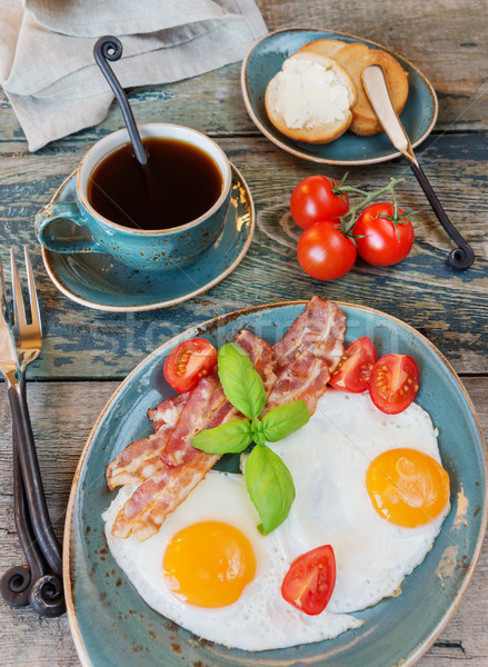 Fried eggs,  bacon, tomato, toast and a cup of coffee Stock photo © Epitavi