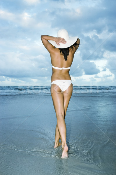 Girl in white bikini walking on beach with white sun hat Stock photo © epstock