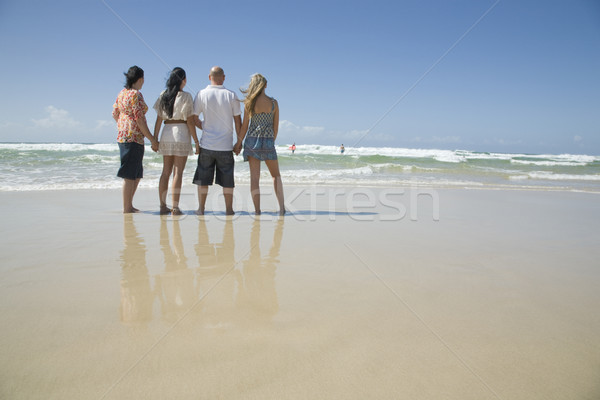 family holding hands looking out to surf Stock photo © epstock