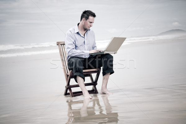 business man sitting on a chair on the beach with laptop Stock photo © epstock
