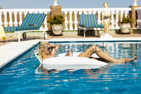 Blonde model chilling in a pool Stock photo © epstock
