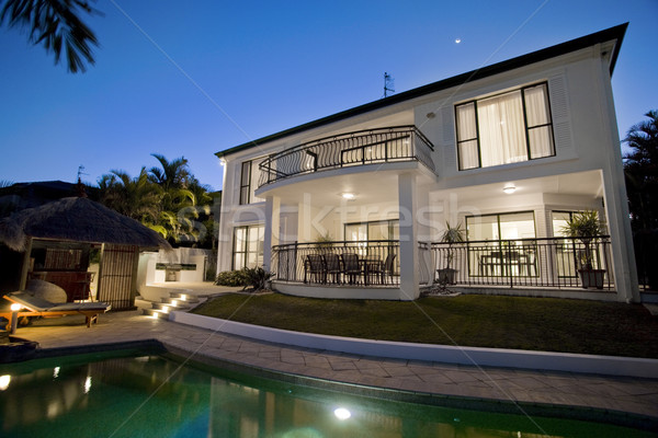 Luxurious mansion exterior at dusk overlooking pool Stock photo © epstock